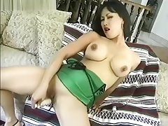 Asian with beamy fake tits plays with a dildo